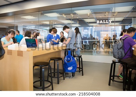 HONG KONG, CHINA - JUNE 15, 2014: Buyers and shop consultants at Apple store in Hong Kong. Store is in a shopping center IFC Mall, it is very popular with locals and tourists visiting Hong Kong. - stock photo