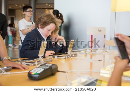 HONG KONG, CHINA - JUNE 15, 2014: Young visitors at Apple store in Hong Kong. Store is in a shopping center IFC Mall, it is very popular with locals and tourists visiting Hong Kong. - stock photo