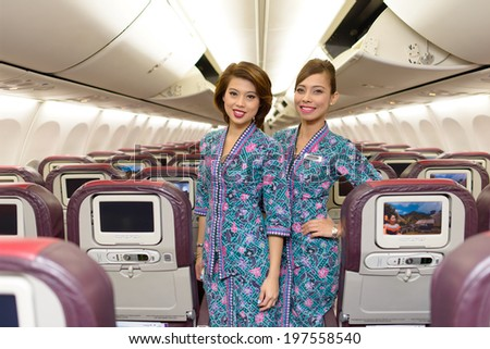 HONG KONG, CHINA - MAY 12, 2014: Malaysian Airline crew members posing in Boeing 737 aircraft after landing on MAY 12, 2014. Malaysian Airline System is the flag carrier airline of Malaysia - stock photo