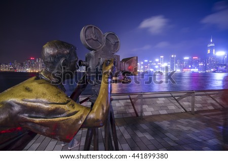HONG KONG, CHINA - NOVEMBER 14 2013: Statue and skyline in Avenue of Stars  in Hong Kong, China. The promenade honours celebrities of the Hong Kong film industry as the famous city attraction. - stock photo