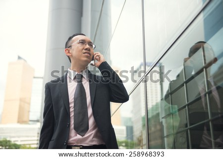 hong kong chinese businessman on a phone in busy central district , vintage tone