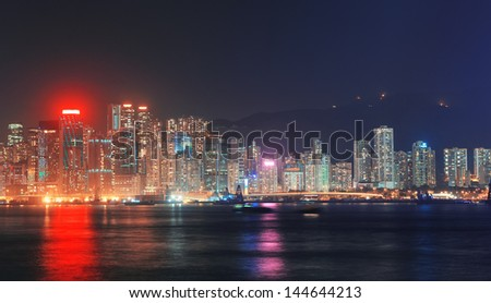Hong Kong city skyline at night over Victoria Harbor with clear sky and urban skyscrapers.