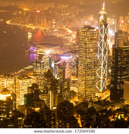 Hong Kong cityscape at night with victoria harbour and large group of tall buildings. - stock photo