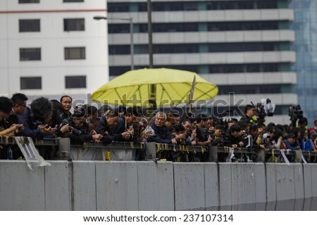 HONG KONG, DEC. 11. 2014: People observe workers remove barricades at an area blocked by pro-democracy protesters near the PLA headquarters, as today is the last day of the protest. - stock photo