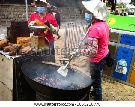 HONG KONG - DECEMBER 08, 2013: Street vendor roasting chestnuts and potatoes in a large wok, popular street snack in Hong Kong
