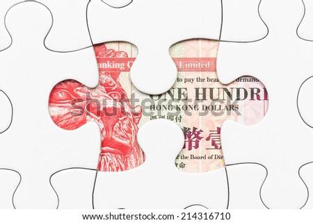 Hong Kong dollar banknote hidden under puzzle financial concept - stock photo