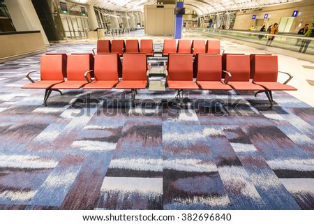 HONG KONG - FEBRUARY 22,2016: The red seats and modern interiors building in departure zone at Hong Kong International Airport.