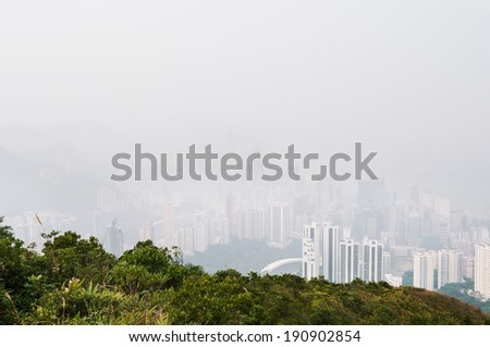 Hong Kong island obscured by haze, as seen from the hills above Happy Valley - stock photo