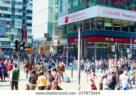 HONG KONG - JAN 19, 2013: People crosing the street in Hong Kong. With a land mass of 1,104 km and population of 7 million people, Hong Kong is one of the most densely populated areas in the world  - stock photo