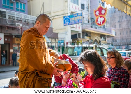 HONG KONG-JAN 10,2016 : Tourists and locals give alms food to monk during the morning on JAN 10 2016 in KOWLOON CITY, HONGKONG
