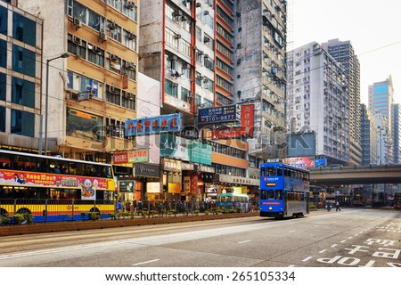 HONG KONG - JANUARY 31, 2015: Decker buses and trams on the central street. Hong Kong is popular tourist destination of Asia and leading financial centre of the world. - stock photo