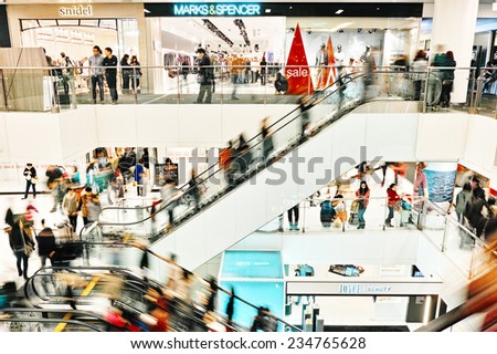HONG KONG - JANUARY 04:  People walk through the shopping mall in Shatin New Town Plaza. New Town Plaza is a shopping mall in the town centre of Sha Tin in Hong Kong. Hong Kong January 04, 2014. - stock photo