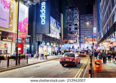 HONG KONG - JANUARY 31, 2015: Taxi and illuminated signs on the street of night city. Hong Kong is popular tourist destination of Asia and leading financial centre of the world