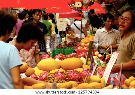 HONG KONG - JULY 08:Chines people shopping at Kowloon City Market on July 08 2004 in Hong Kong, China. It's one of the largest food markets in Hong Kong. - stock photo