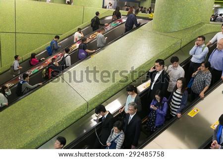 HONG KONG - MAR 30 : Tourists and locals escalator down to the subway on March 30,2015 at MTR hong kong - stock photo