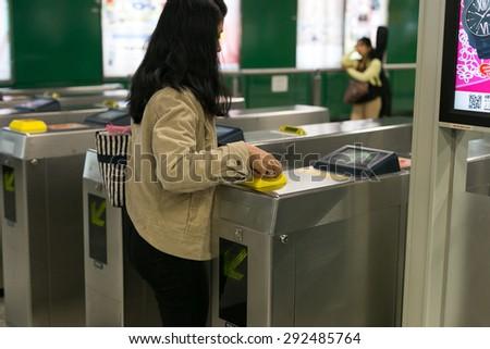 HONG KONG - MAR 29 : Woman walks through the scanner subway tickets on March 29,2015 at MTR hong kong - stock photo