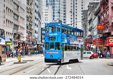 HONG KONG - MARCH 30: An electric tram turns into Des Voeux Road Mar. 30, 2015. These historic streetcars have been in operation since 1904 and are the world's only double-decker tram system. - stock photo