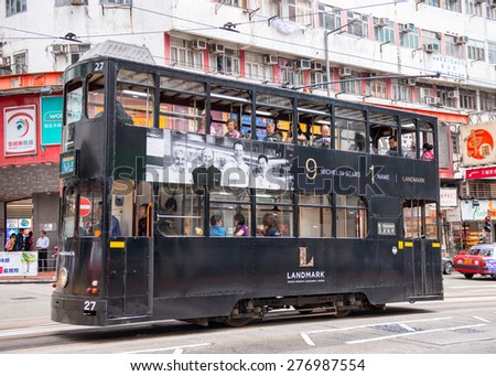 HONG KONG - MAY 11, 2014: Black double-decker tram in a city street. Trams also a major tourist attraction and one of the most environmentally friendly way of travelling in Hong Kong. - stock photo