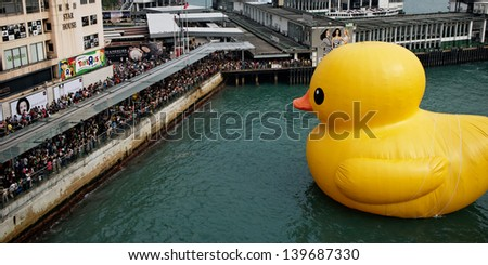 HONG KONG - MAY 11:Giant Rubber Duck looking at people in Victoria harbor on 11 May 2013 in Hong Kong. The 50 ft high inflatable duck is created by the Dutch artist Florentijn Hofman. - stock photo