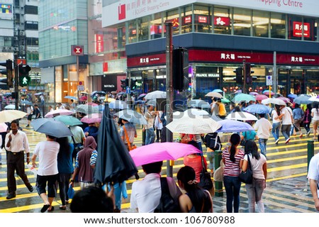 HONG KONG - MAY 20: People in the rain on May 20, 2012 in Hong Kong. With a land mass of 1,104 km and population of 7 million people, Hong Kong is one of the most densely populated areas in the world - stock photo