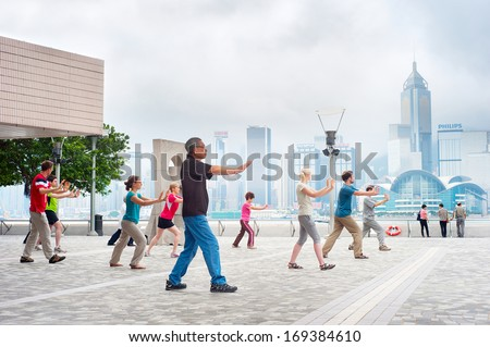 HONG KONG - MAY 15: Tai Chi Exercising in the morning on May 15, 2013 in Hong Kong. With a land of 1,104 km and population of 7 million, Hong Kong is one of most densely populated areas in the world - stock photo
