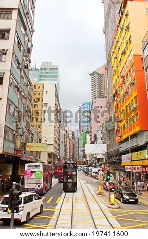 HONG KONG - MAY 15, 2014: Unidentified people are walking on the street in Hong Kong. With a 7 million people, Hong Kong is one of the most densely populated areas in the world - stock photo