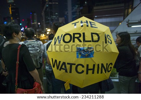 "HONG KONG - OCT 5: A lady is holding an umbrella which shows ""The World is Watching"" during Occupy Central movement in Hong Kong on October 5 2014."