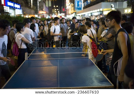 HONG KONG - OCT 15: People gather together and play table tennis in the middle of the road during Occupy Central movement in Mongkok in Hong Kong on October 15 2014. - stock photo