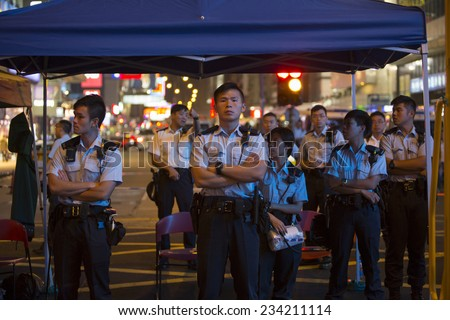 HONG KONG - OCT 15: Policemen are standing by at the other side of barricades in the middle of the road in Mongkok in Hong Kong on October 15 2014. Mongkok is the busiest district in Hong Kong. - stock photo