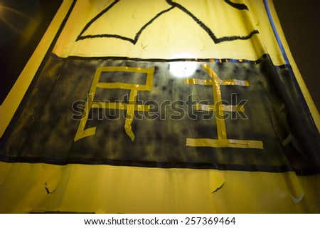 """HONG KONG - OCT 15: Slogan with the Chinese """"democracy""""  is hung in the middle of the road in Mongkok in Hong Kong on October 15 2014. Mongkok is the busiest district in Hong Kong.  - stock photo"""