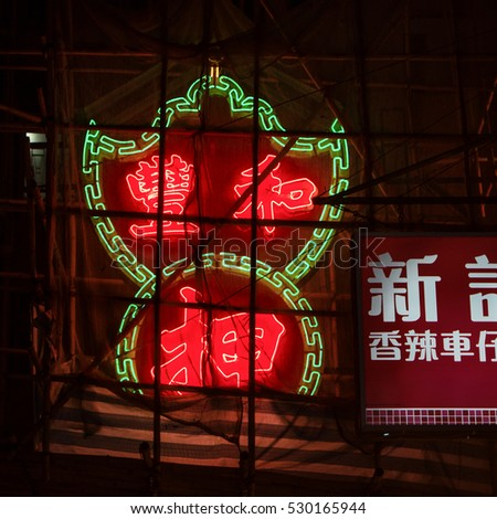 HONG KONG - October 2016: Neon signboard glowing at night covered by fabric and bamboo scaffolding.