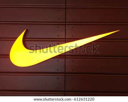 HONG KONG on 31ST MARCH 2017. Yellow Nike logo over brown background. Nike, Inc. is an American multinational corporation that designs, develops, manufactures and sells footwear and other items