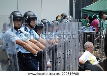 HONG KONG - SEP.27: around 100 protesters climb over the fence to reclaim the Civic Square. Riot police are deployed at the main entrance of the square - stock photo