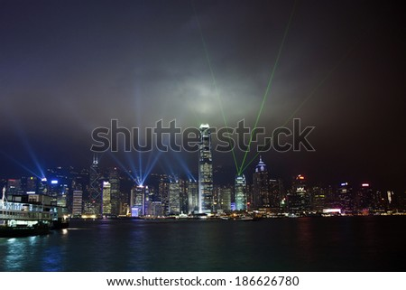 Hong Kong skyline at night with lights and skyscrapers over sea with laser beams