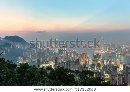 Hong Kong skyline shot after sunset from the top of a mountain in Hong Kong island. The view goes through the Victoria harbor until Kowloon.