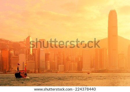 Hong Kong skyline with boats in Victoria Harbor in red tone.  - stock photo