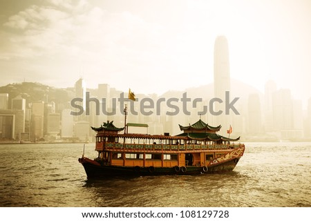 Hong Kong skyline with boats in Victoria Harbor in yellow tone. - stock photo