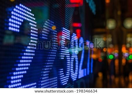 Hong Kong stock market price display at street in the night. - stock photo