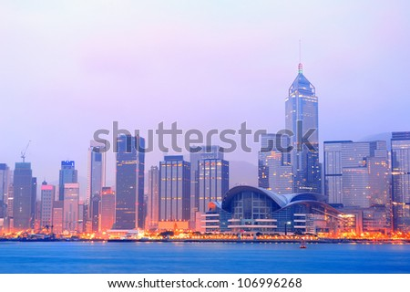 Hong Kong Victoria Harbor morning with urban skyscrapers over sea with blue tone and street light. - stock photo