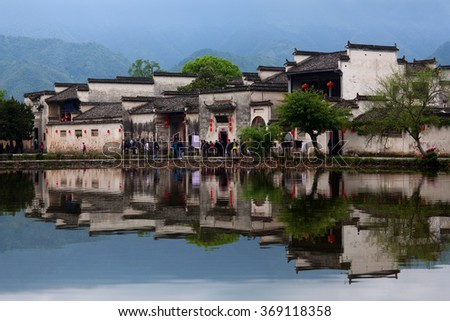 HONGCUN, CHINA - APRIL 20: Tourist walking around Moon Lake in Hongcun Village, China on April 20, 2014. Hongcun is ancient village in Anhui Province, near the southwest slope of Mount Huangshan.