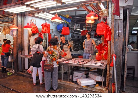HONGKONG, CHINA-MAY 23: Shoppers at a fish shops in Wan Chai. These shops are a city landmark and operate since the 19 century. May 23, 2007 Hong Kong, China - stock photo