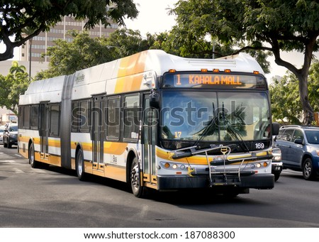 HONOLULU - APRIL 2, 2014: A Hybrid bus rides through Honolulu on April 2, 2014  The city of Honolulu purchased 60 clean diesel buses during 2013 to be more environmentally friendly. - stock photo