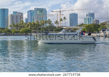 Honolulu, Hawaii, USA, April 8, 2015:  Motorboat on a harbor cruise in Honolulu Hawaii inside the  Ala Wai Small Boat Harbor on a clear and calm morning.   - stock photo