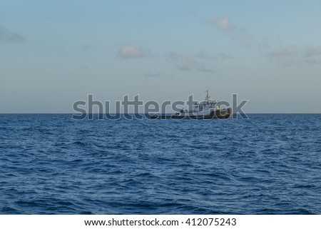 Honolulu, Hawaii, USA, April 27, 2016:  Seascape view of an ocean going tugboat against a Waikiki horizon.