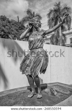 Honolulu, Hawaii, USA, April 12, 2015: The Honolulu Hula Maiden greets visitors to the Port of Honolulu at Aloha Tower.  The statue is over eight feet tall and made of bronze. - stock photo
