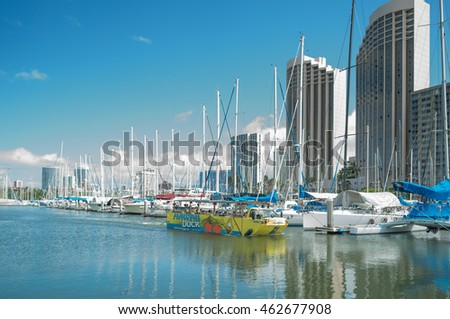 Honolulu, Hawaii, USA, August 2, 2016:  An Amphibious Duck tourist ride goes on tour of the Ala Wai Harbor with the Ala Moana Shopping Center in the backdrop.
