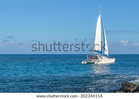 Honolulu, Hawaii, USA, August 2, 2015: Evening departure of a catamaran under full sail from Honolulu and headed for the island of Kauai.  Catamarans are increasingly popular in the Hawaiian Islands. - stock photo