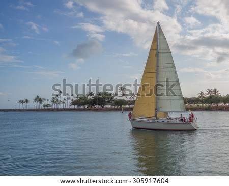 Honolulu, Hawaii, USA, August 14, 2015:  Evening view of a sailboat and crew sailing in the Ala Wai Lagoon.  The Ala Wai Harbor is the largest pleasure boat harbor in Hawaii.