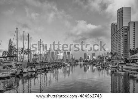 Honolulu, Hawaii, USA, August 6, 2016:  Morning panorama of Waikiki hotels built to the edge of the Ala Wai Harbor in tones of black and white.