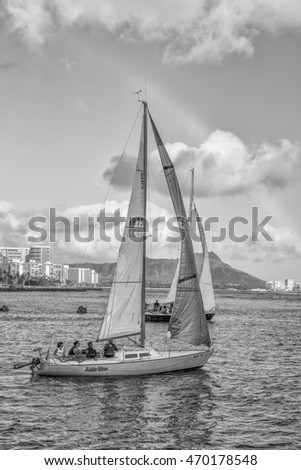 Honolulu, Hawaii, USA, August 17, 2016:  Profile view of a sailboat the crew sailing in Waikiki with hotels and Diamond Head Crater in the background.